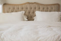 Empty bed with white duvet cover in bright bedroom Royalty Free Stock Photos