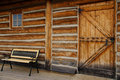 Empty bench log cabin door window in front of with and setting on wooden walkway Royalty Free Stock Photos