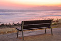 Empty bench beside the sea at sunset. Royalty Free Stock Photo