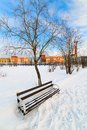 An empty bench in the snow-covered city park. Royalty Free Stock Photos