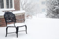 Empty black bench in snow an wrought iron a storm by a brick building Stock Images