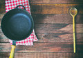 Empty black cast-iron frying pan and wooden spoon Royalty Free Stock Photo