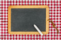 Empty blackboard with chalk on a checkered table cloth red Royalty Free Stock Image