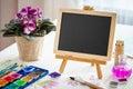 Empty blackboard, flower in pot and watercolor paints