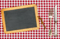 Empty blackboard with silverware on a tablecloth checkered Royalty Free Stock Image