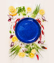 Empty blue plate with fresh seasoning and spices on withe rustical wooden background top view place for text Royalty Free Stock Photos
