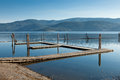 Empty boat dock an wooden in late summer with haze around the mountains across the calm lake Royalty Free Stock Image