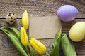 Empty brown card, Easter eggs and tulips on a old wooden table.