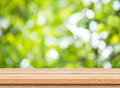 Empty brown wood table top with blur green tree bokeh background Royalty Free Stock Photo