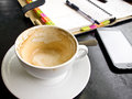 Empty capuchino coffee cup with notebook and telephone Stock Image