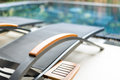 Empty chaise longues near swimming pool metal lounges in hotel area blurry with clear water in background relaxation and Royalty Free Stock Image