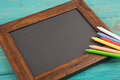 empty chalkboard with copyspace and colorful crayons on wooden table Royalty Free Stock Photo