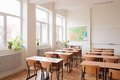 Empty classroom interior with wooden desks and chairs maps and white board Stock Photography