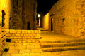 Empty cobblestone street at night an narrow back alley with lighting Stock Images