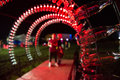 Empty Coca Cola bottles are arranged and illuminated with red li