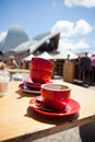 Empty coffee cups on outdoor cafe table closeup of red with sydney opera house in background Royalty Free Stock Photo