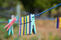 Empty colorful clothes pegs on string in garden Royalty Free Stock Photo