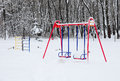 Empty Colorful Swing in Winter Time with Snow Outdoor. Royalty Free Stock Photo