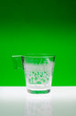 Almost empty cup glass with traces of milk on green background Stock Photos