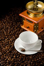 Empty cup and grinder on coffee beans Stock Image