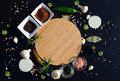 Empty cutting board and pepper, bay leaf, rosemary, onions, Himalayan salt, olive oil, soy sauce on a black backg Royalty Free Stock Photo