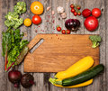 Empty cutting board and vegetables on weathered wooden backgroun Royalty Free Stock Photo