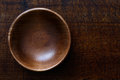 Empty dark wooden bowl isolated on dark brown wood. Royalty Free Stock Photo