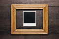 Empty frame and old photo on wooden background Royalty Free Stock Photo