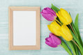 Empty frame and tulip flowers on rustic table for March 8, International Womens day, Birthday or Mothers day