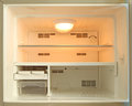 Empty freezer of refrigerator and orange light bulb inside Stock Image