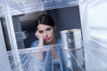 Empty fridge young sad woman looking at one tin in her Royalty Free Stock Photo