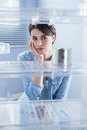 Empty fridge young sad woman looking at one tin in her Royalty Free Stock Images