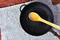 Empty frying pan with a wooden spoon Royalty Free Stock Photo