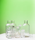 Empty glass bottles on green with space for your text or logo Stock Photos