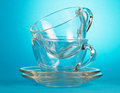 Empty glass cups and saucers on blue background Royalty Free Stock Photos