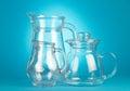 Empty glass pitchers three on blue background Stock Photo