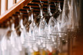Empty glasses for wine above a bar rack. Hanging wine glasses in Royalty Free Stock Photo