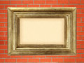 Empty golden wooden frame on the red brick wall Royalty Free Stock Photo