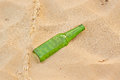 Empty green beer bottle on beach the yellow sand of the Royalty Free Stock Images