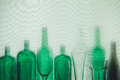 Empty green glass bottles and beer glasses stand in row Drink Concept Royalty Free Stock Photo