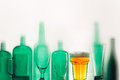 Empty green glass bottles and a glass of beer stand in row Drink Concept Royalty Free Stock Photo
