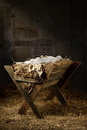 Empty manger in stable filled with hay with baby soft cloths on top Stock Photos