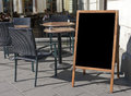 Empty menu board stand and outdoor cafe Stock Photography