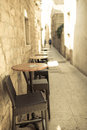 Empty narrow street of old town with caffee tables outdoors sandstone buildings in foreground table and chairs outdoor photo Stock Photography