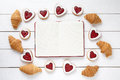 Empty notebook frame for design text, croissants and heart shaped cookies composition on Valentines Day Royalty Free Stock Photo