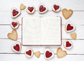 Empty notebook frame for design text and heart shaped cookies on white wooden background. Royalty Free Stock Photo