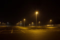 Empty outdoor car park at night shined with street lamps. Royalty Free Stock Photo