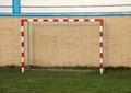 Empty outdoor handball goal with wall in background on green field Royalty Free Stock Photos
