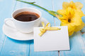 Empty paper card, coffee and yellow flower on blue colored woode Royalty Free Stock Photo