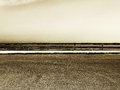 Empty parking with guardrail grainy sepia hue a detail of an a just in the middle of it a cloudy sky in the background landscape Royalty Free Stock Photo